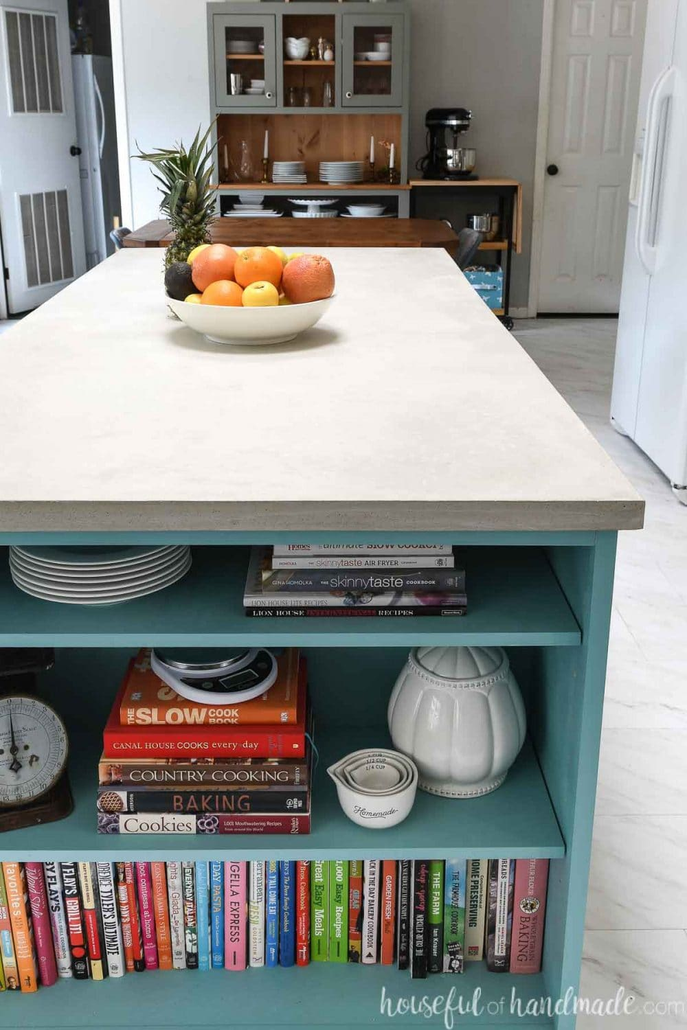 Looking down the kitchen island with a bookshelf on the end and a DIY concrete countertop made from RapidSet concrete on the top.