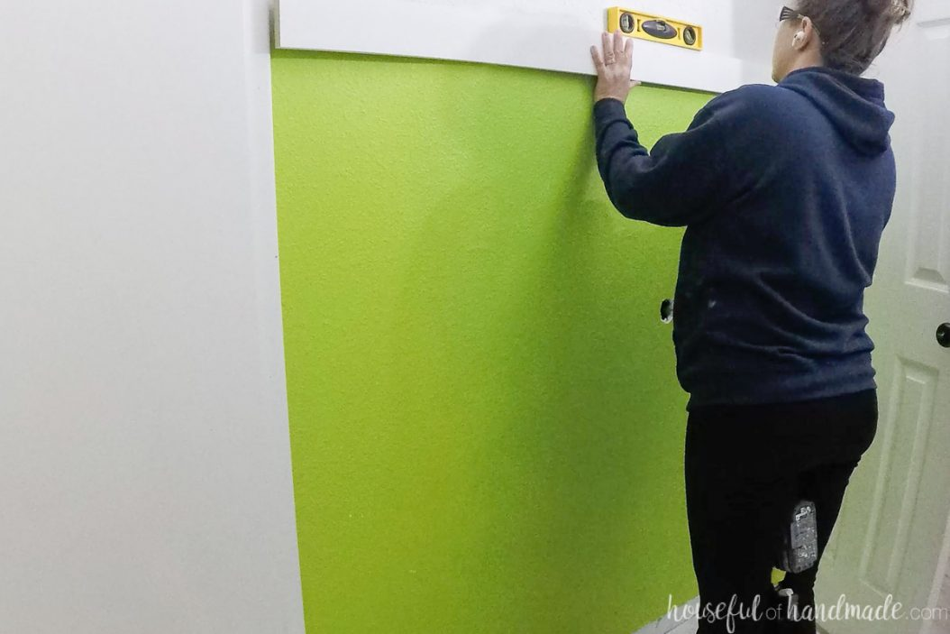 Leveling the top board on the wall with a level.