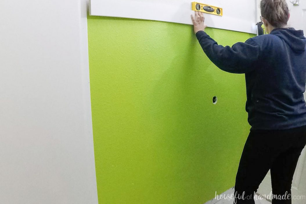 Attaching the first board to the wall with a Ryobi battery powered nail gun.