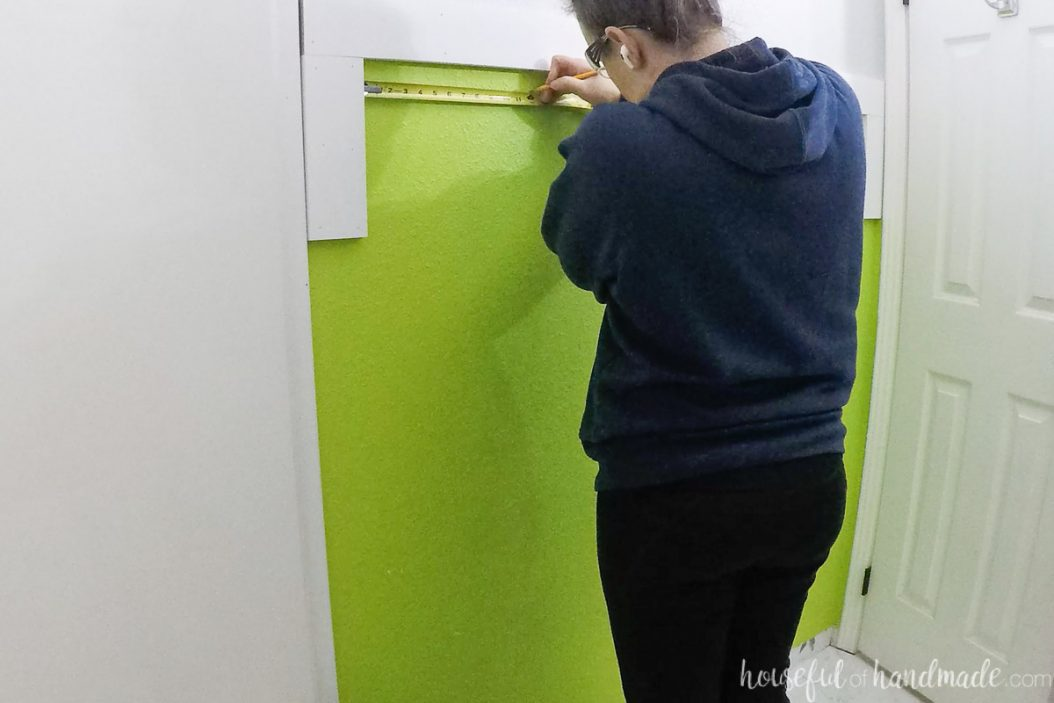 Measuring to attach the smaller vertical boards to the wall.