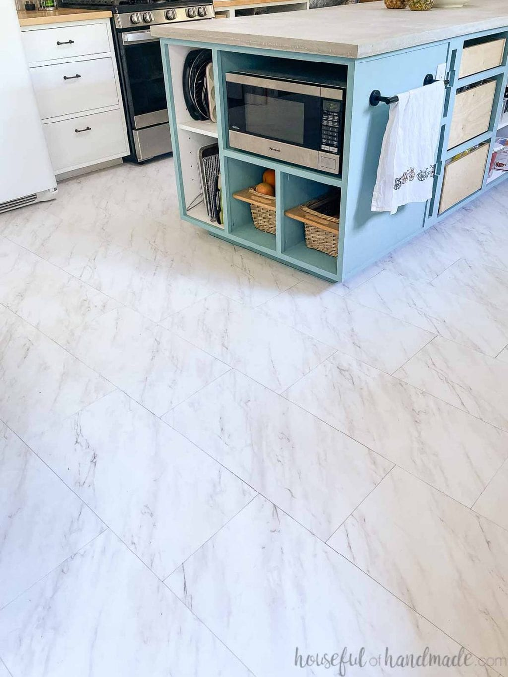 Marble look peel and stick vinyl tiles installed on the floor in a kitchen and dining room.