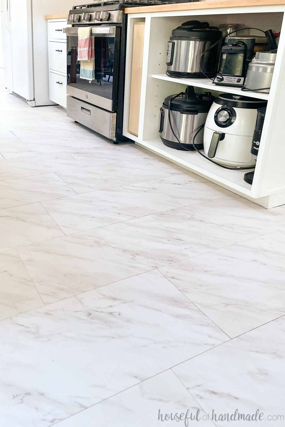 Peel and stick vinyl tiles that look like white marble with gray veining on the floor in a DIY kitchen.