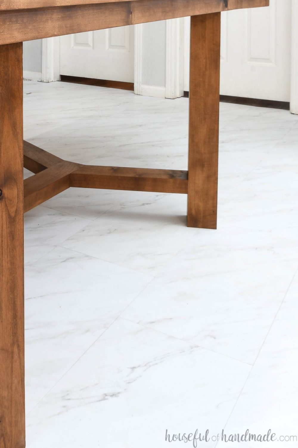 Close up of the grecian marble look vinyl tile installed in the dining room under a rustic table.