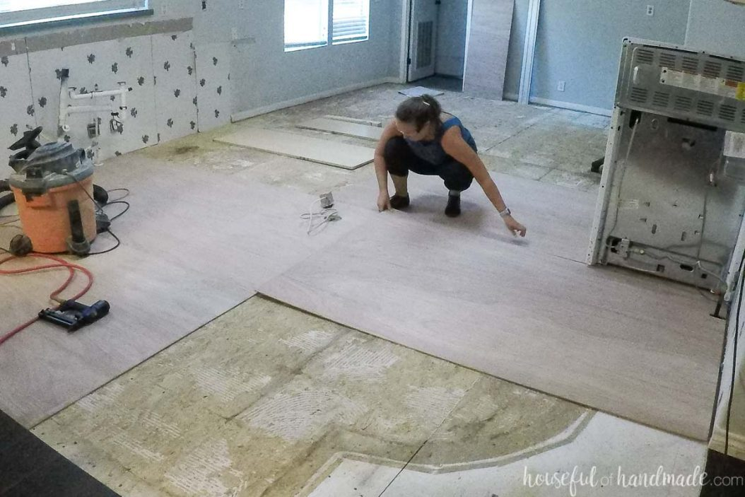 Laying the 4x8 sheets of underlayment over the demoed floor with the seams staggered.