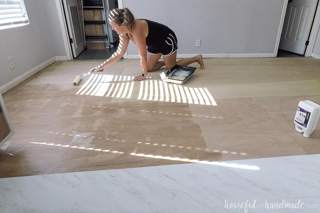 Applying roll on vinyl tile adhesive with a paint roller.