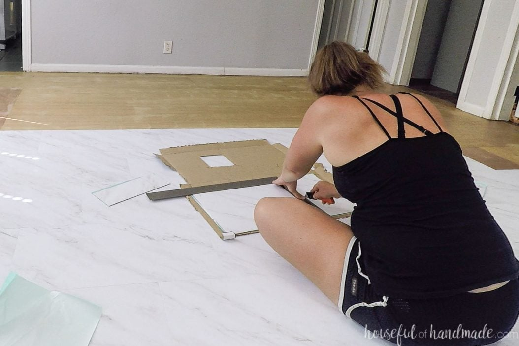 Scoring the cut line of the vinyl tile with a utility knife and a straight edge.