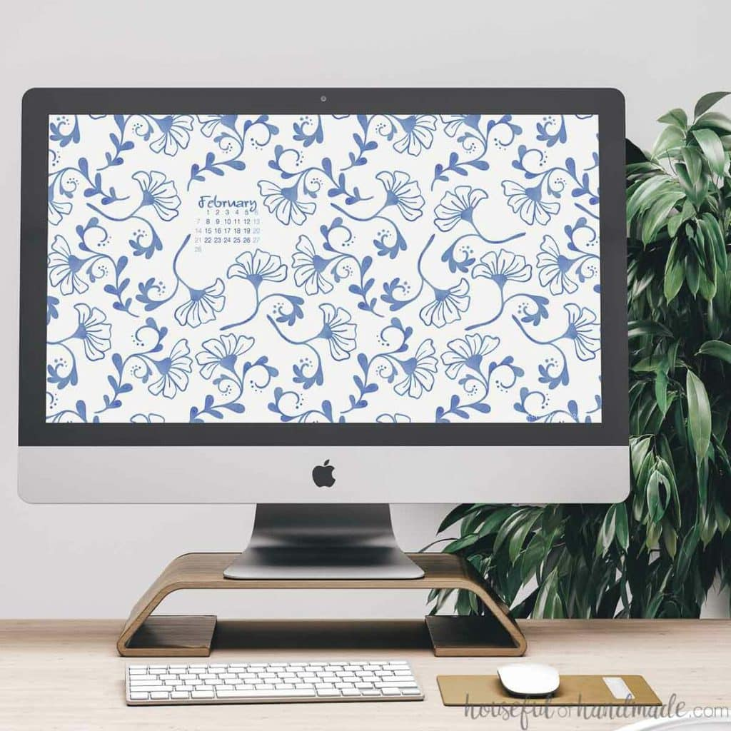 iMac computer on a desk with the blue floral free digital background for February on the screen.