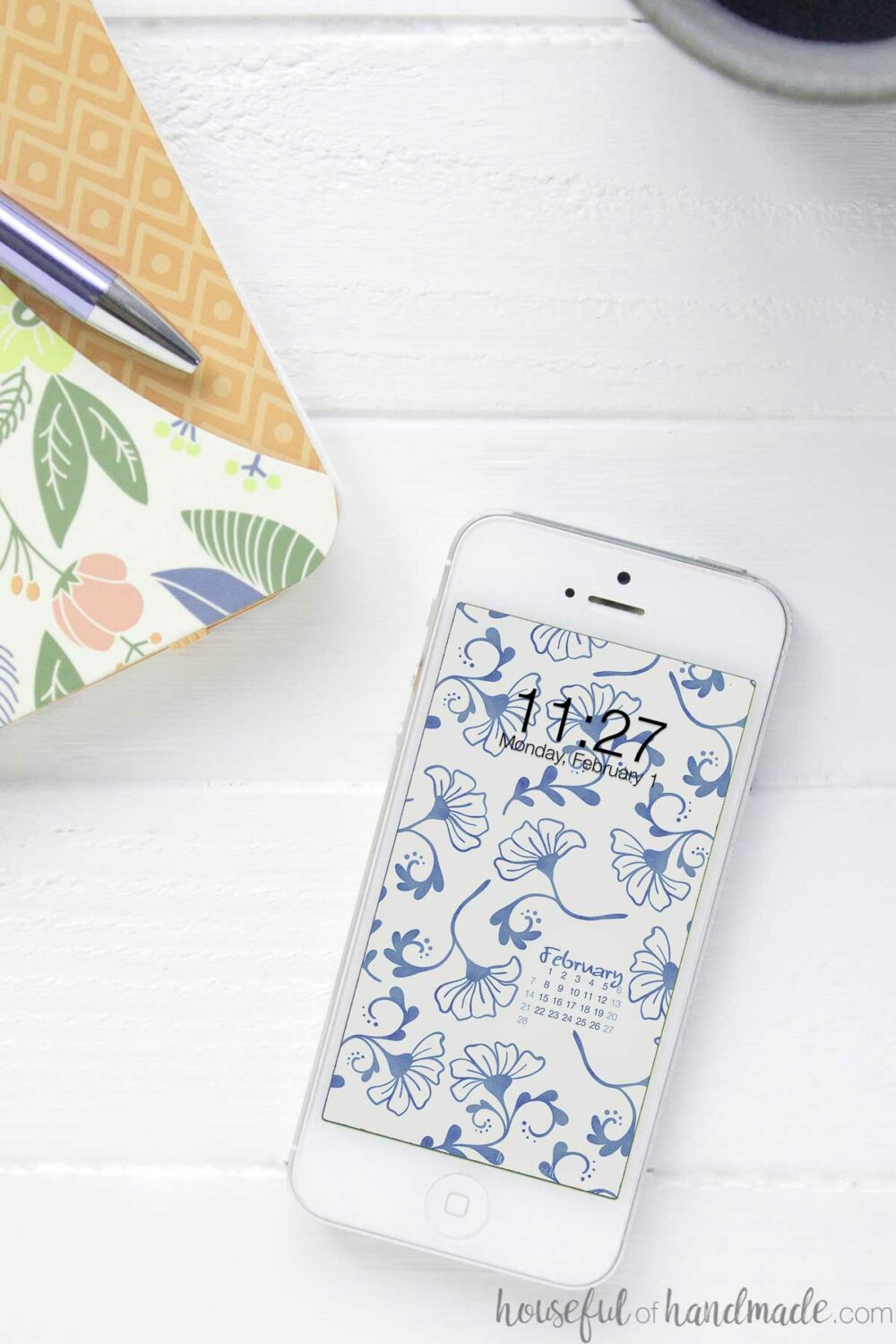 White iPhone with blue floral pattern on the screen as a digital wallpaper with a February calendar.