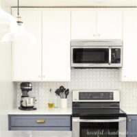 Kitchen with full height white kitchen wall cabinets and soft navy blue base cabinets.