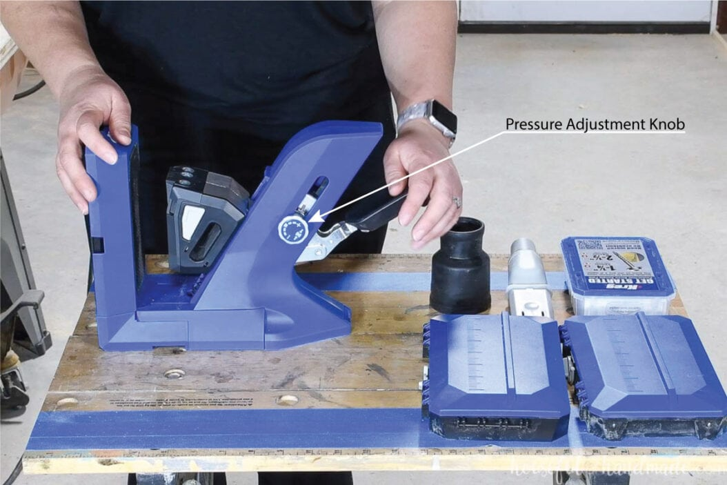 The side of the new Kreg jig with an arrow pointing at the pressure adjustment knob for the auto clamp.