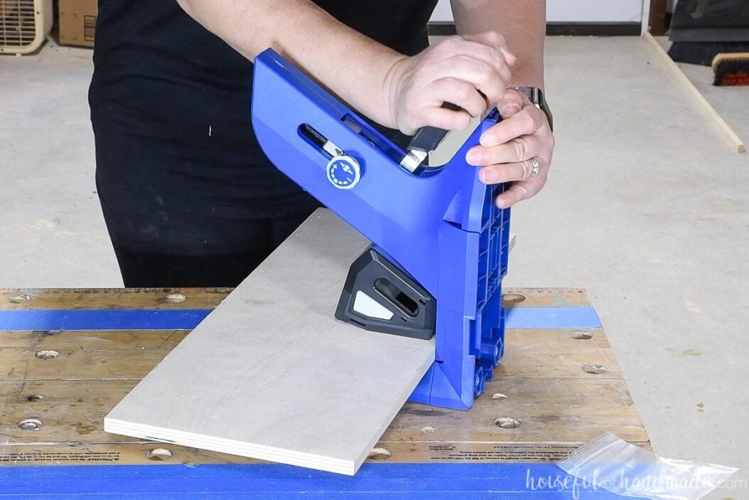 """The new Kreg pocket hole jog set up horizontally with a piece of 1/2"""" plywood clamped in the jig."""