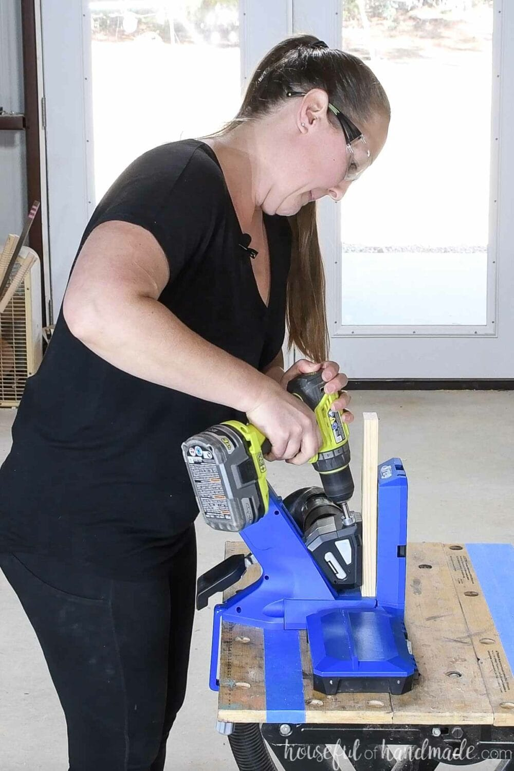 """Kati drilling a pocket hole into a 3/4"""" thick board using the Kreg Jig 720Pro."""