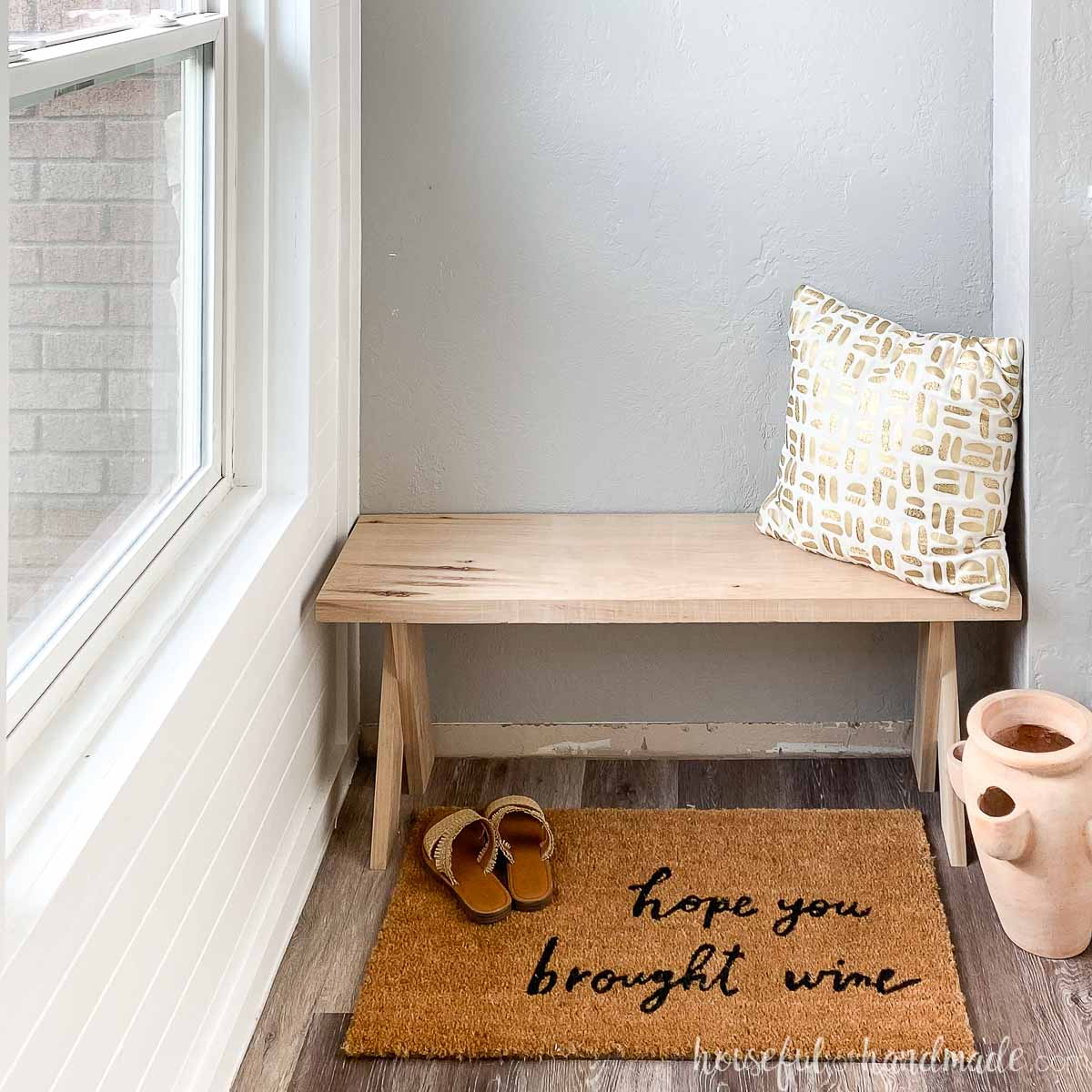 """DIY x-leg bench made from hickory wood in an entryway with driftwood vinyl flooring and """"hope you brought wine"""" rug in front with accessories."""