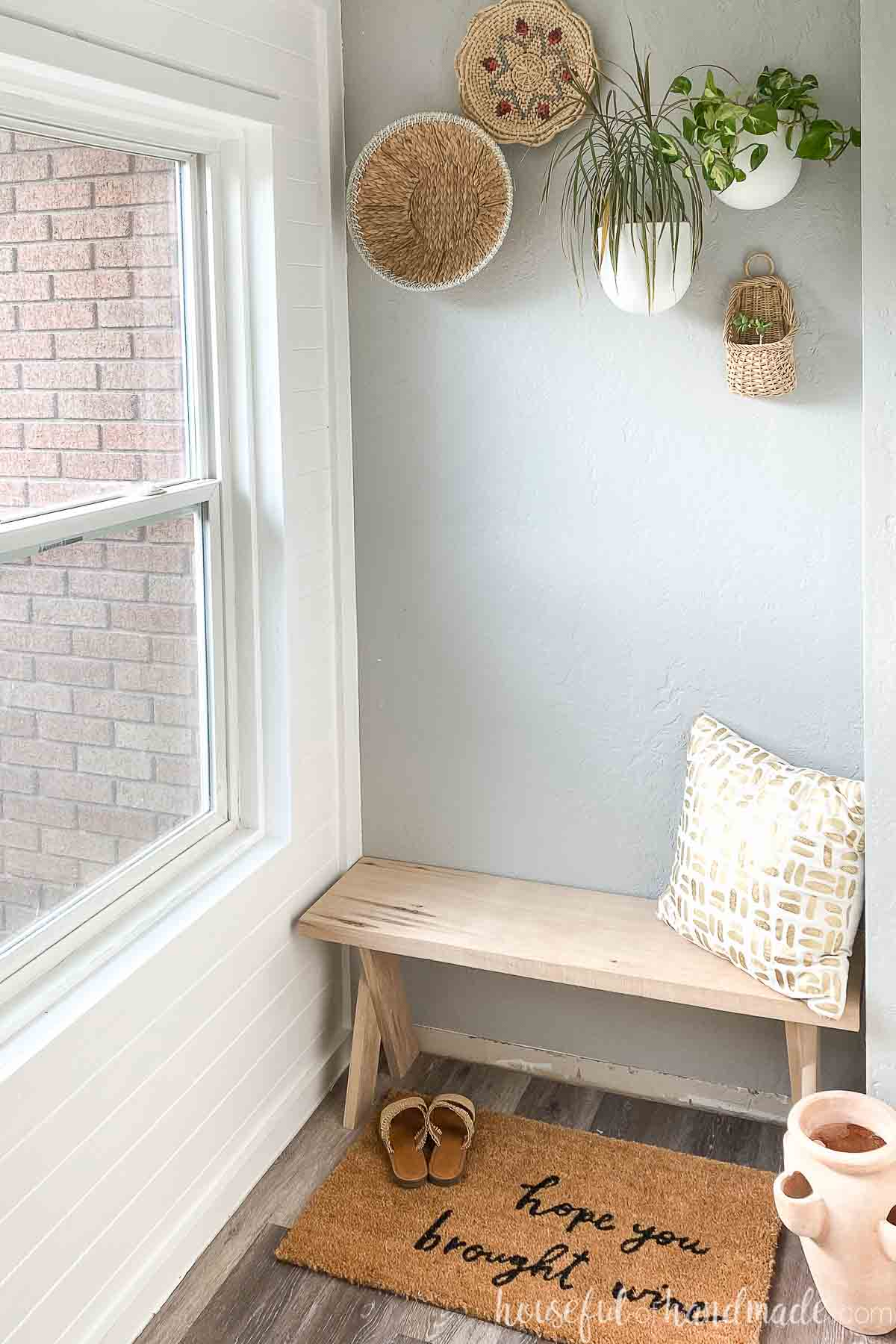 Entryway with x-leg bench from lightwood and gold/white pillow, adobe planter, rug and sandals around it.