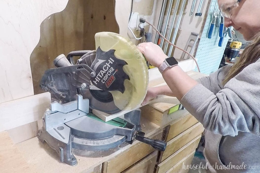 Cutting the legs for the bench with a miter saw at an angle.