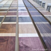 Looking down boards of different wood species with blocks of different colored stains on them.