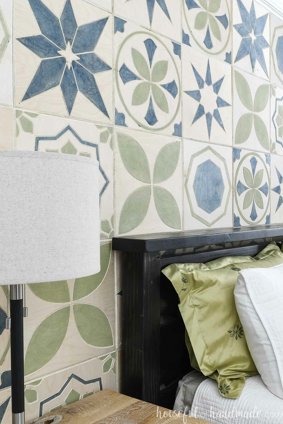 Angled view of the patterned tile DIY accent wall installed on the wall behind a bed.