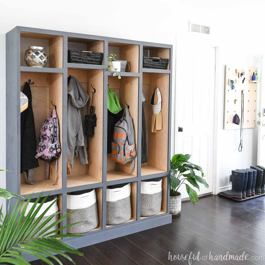 DIY storage cabinet with 4 locker sections for storing coats, shoes, backpacks, and more in a room with white walls and dark wood floors.