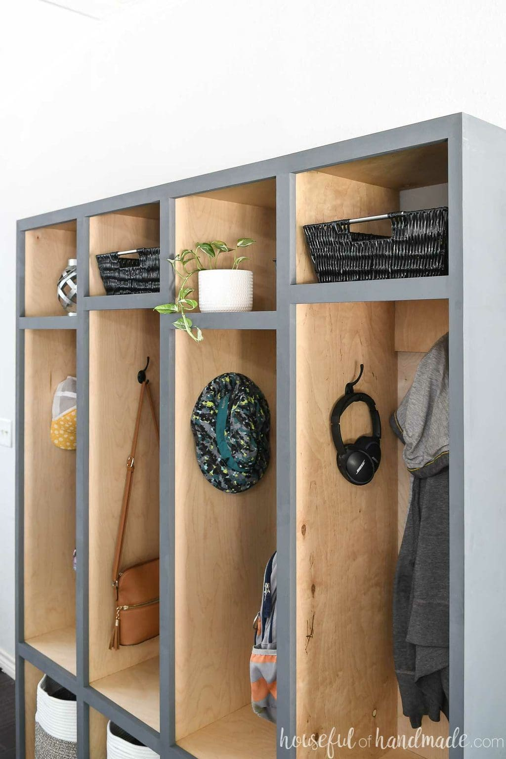 Close up of the upper shelves in the mudroom storage lockers with storage baskets and decor in them.