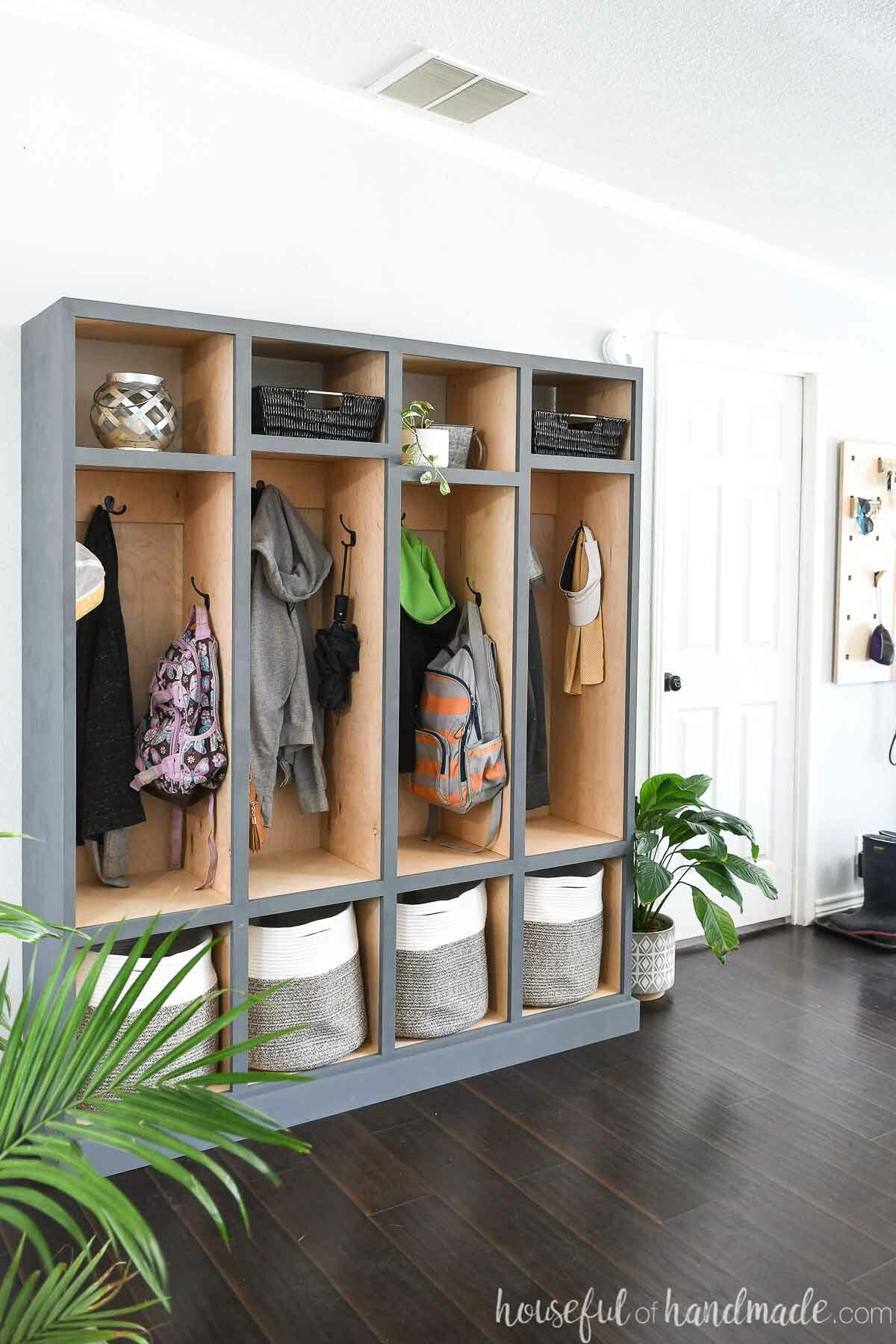 DIY mudroom storage lockers with natural wood tone on the inside and gray-blue painted outside in an entryway filled with coats and backpacks.
