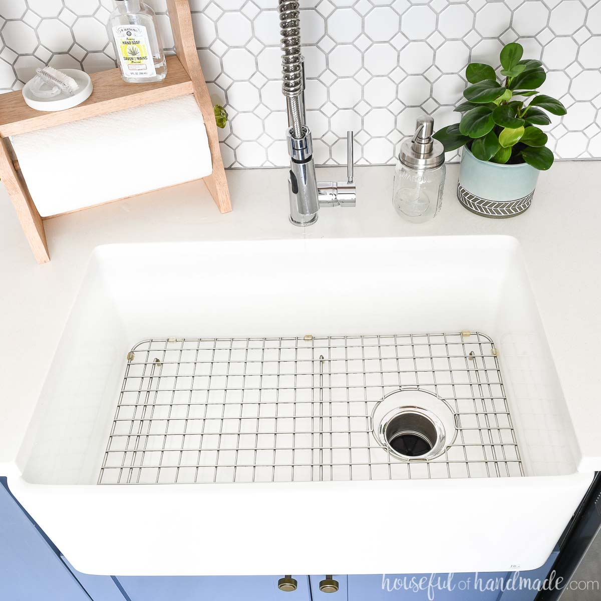 White farmhouse sink installed in a blue base cabinet with a metal grate in the bottom.