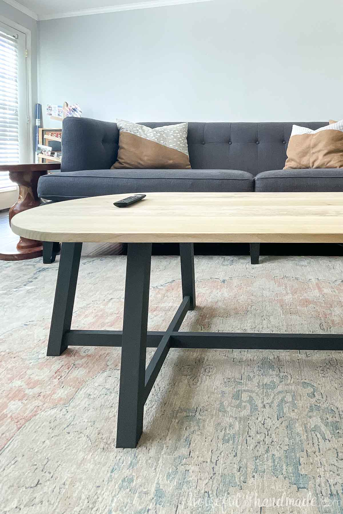 Close up of the left side of the coffee table in front of the sofa with a charcoal painted base.
