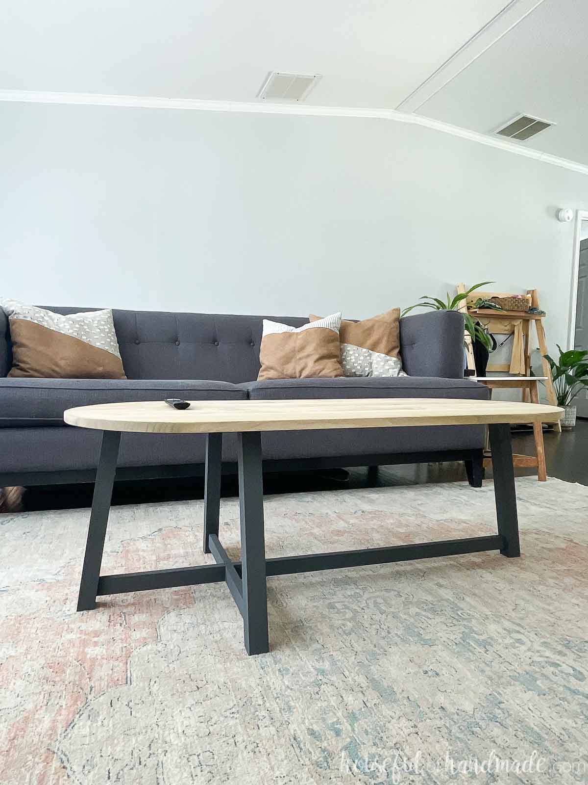 Asymmetrical coffee table with charcoal painted base and light stained wood rounded top in a living room.