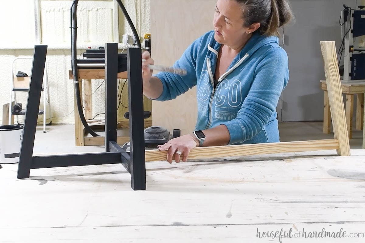 Painting the asymmetrical base of the coffee table with charcoal chalked paint.