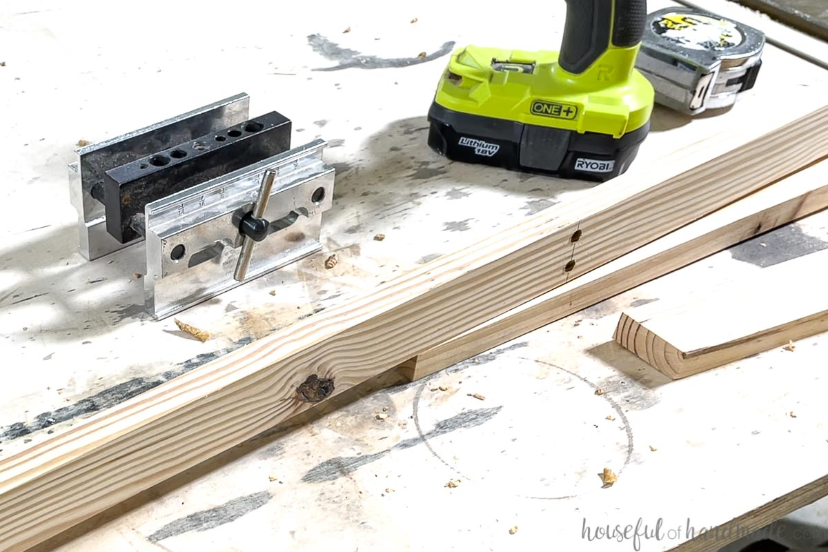 Two holes drilled through the 1x2 piece for the coffee table base sitting on a work bench.