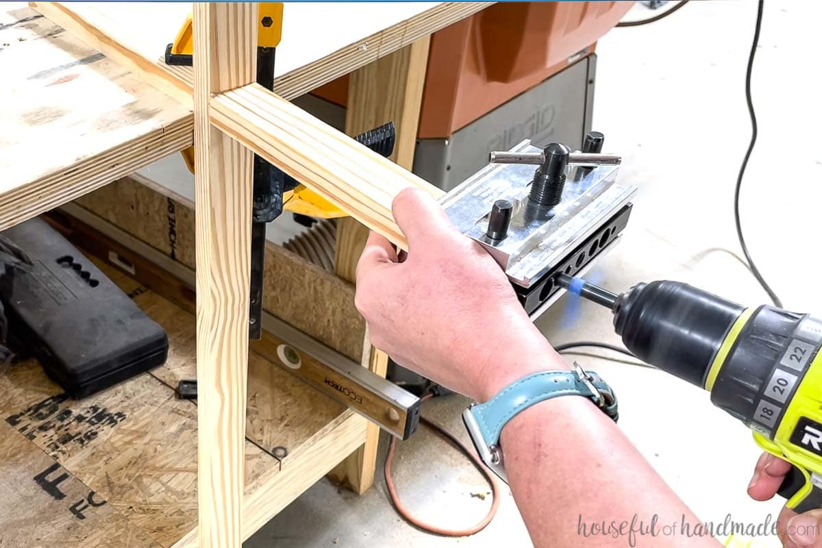 Drilling holes for dowel pins in the end of the coffee table base with a self-centering doweling jig.