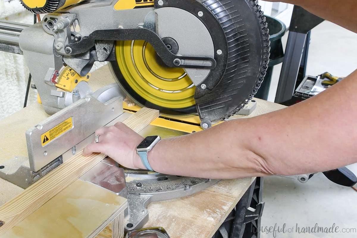 Cutting a 1x2 board on a miter saw.
