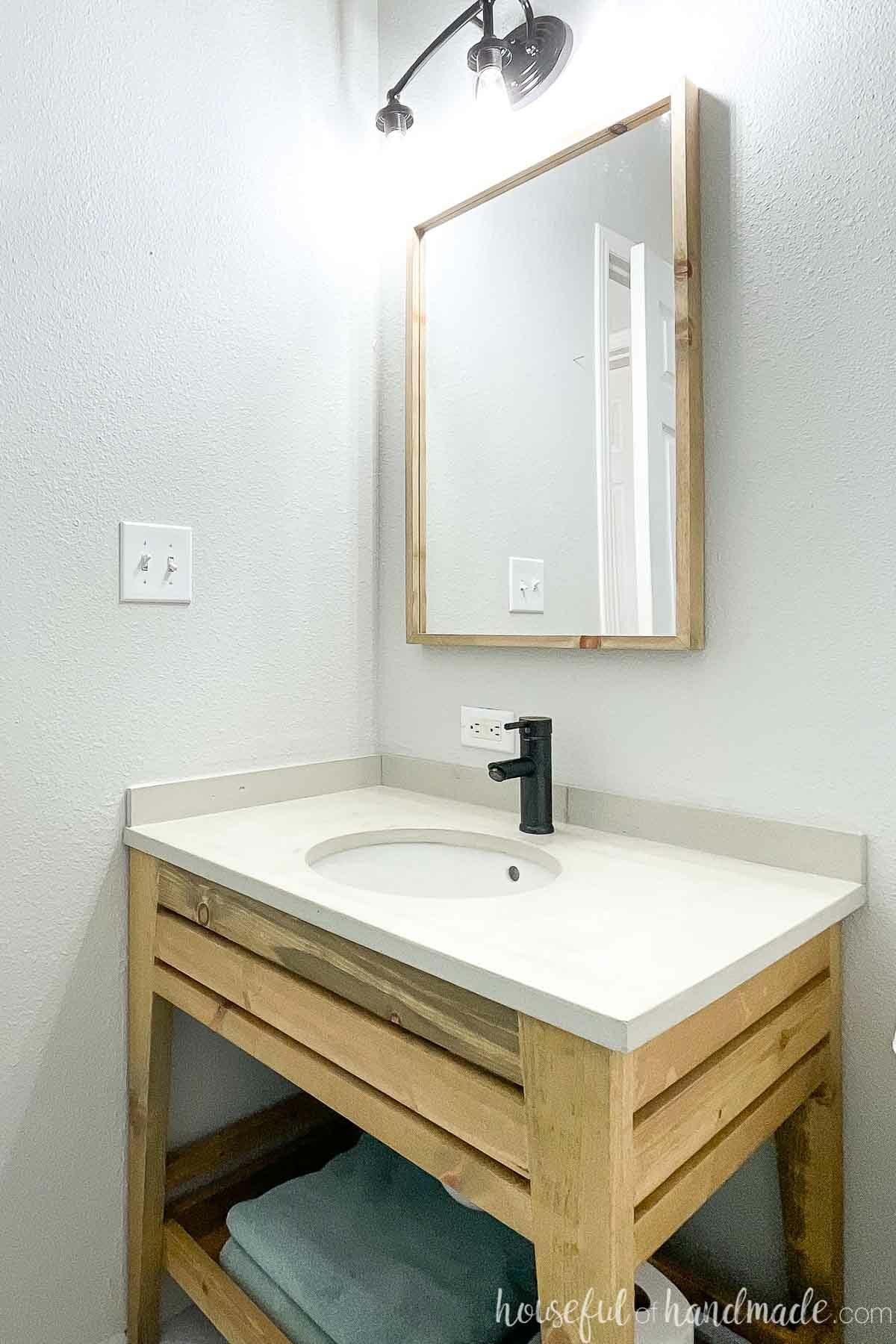 Corner view of the budget bathroom vanity remodel showing the DIY concrete vanity top on the open wood vanity.