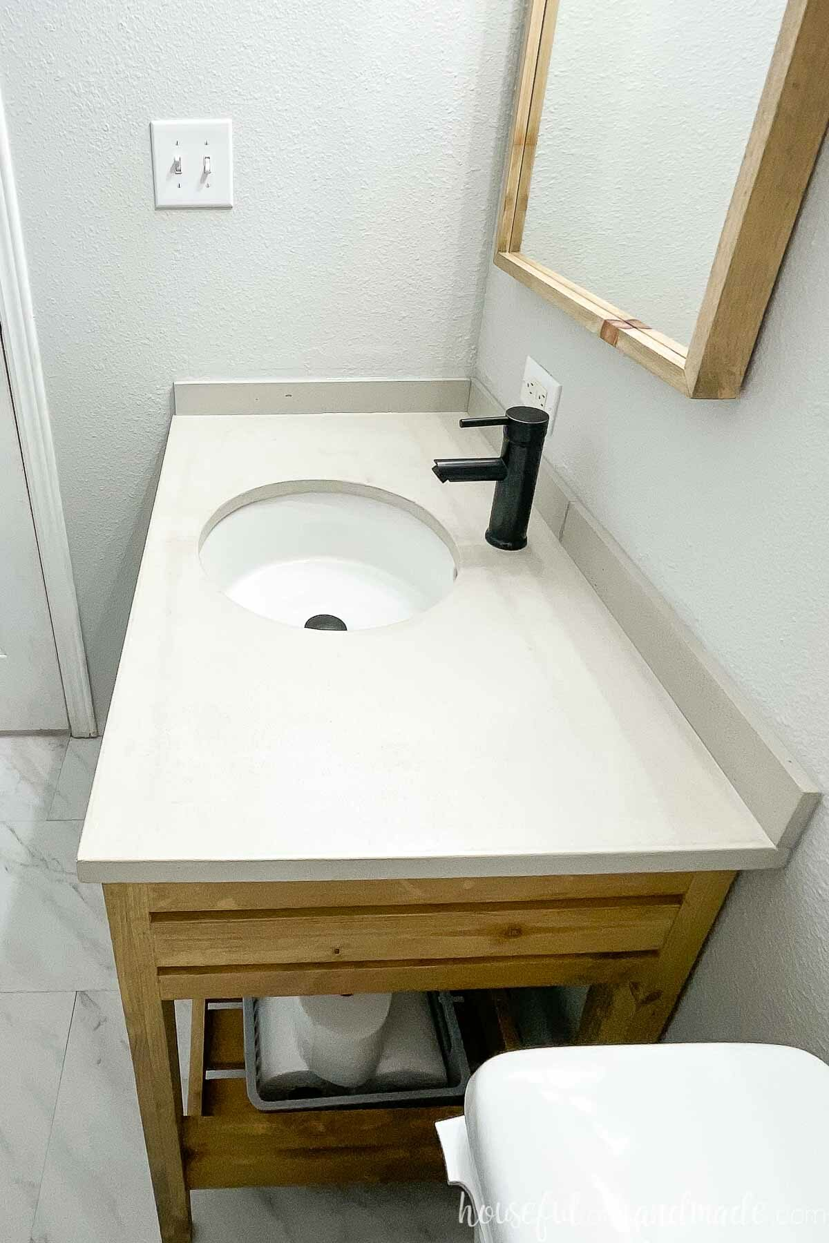 Side view of the concrete vanity top with a white undermount sink and black faucet.
