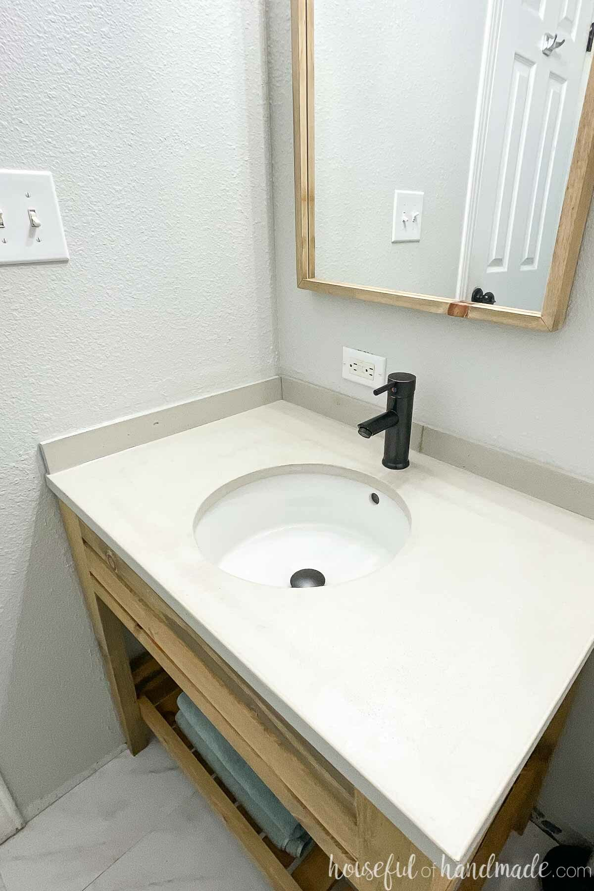 Angled view of the top of the concrete vanity top installed on the wood vanity in the bathroom remodel.