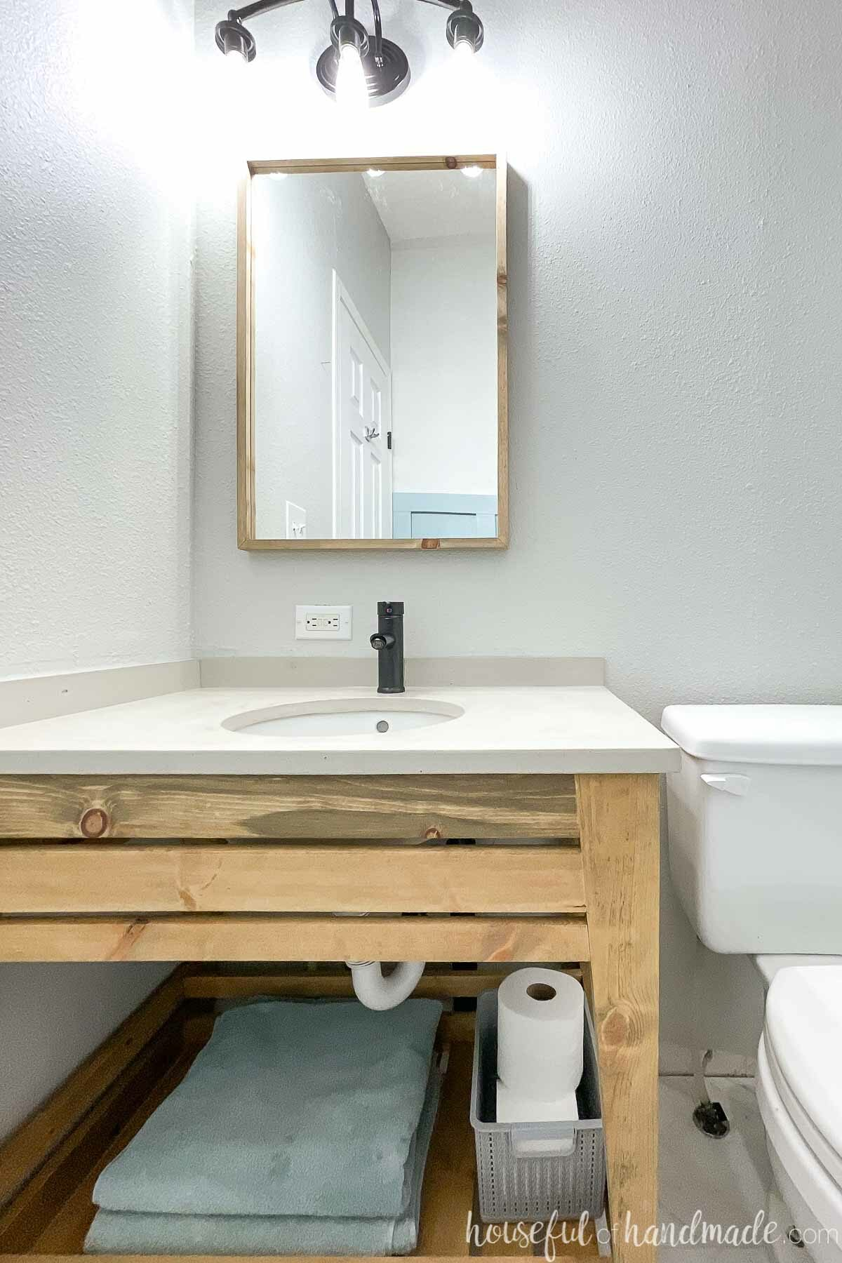 Open modern wood bathroom vanity with concrete vanity top, thin wood framed mirror and black fixtures in a bathroom.