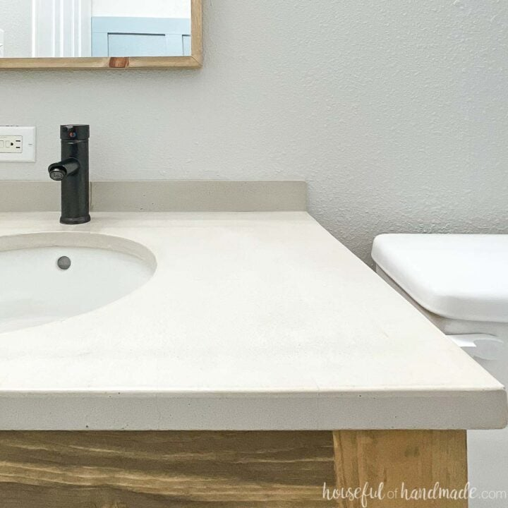 Right half of the DIY concrete vanity top installed on top of a wood vanity with and undermount sink and black faucet.
