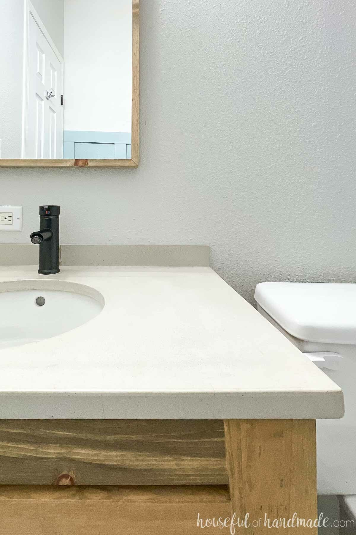 Half of the DIY concrete countertop installed on an open vanity with a black faucet and white undermount sink.