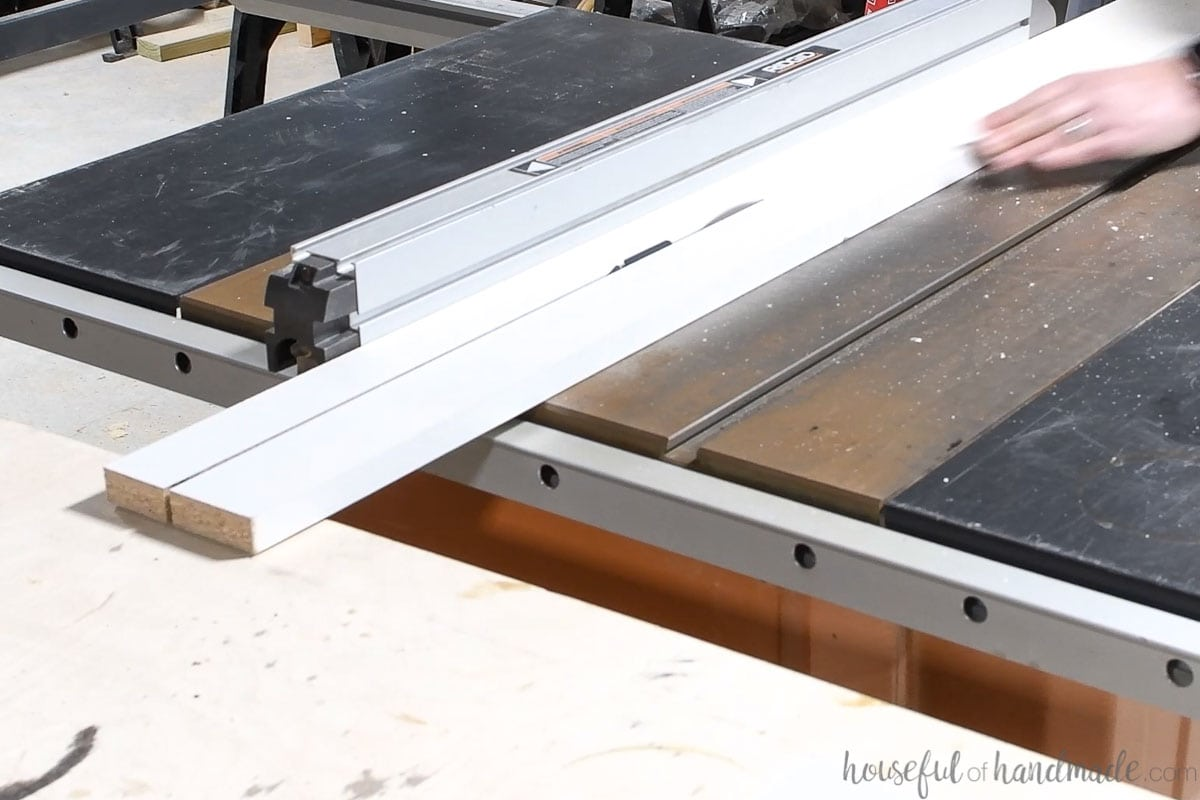 Ripping thin strips of the melamine covered board on a table saw.