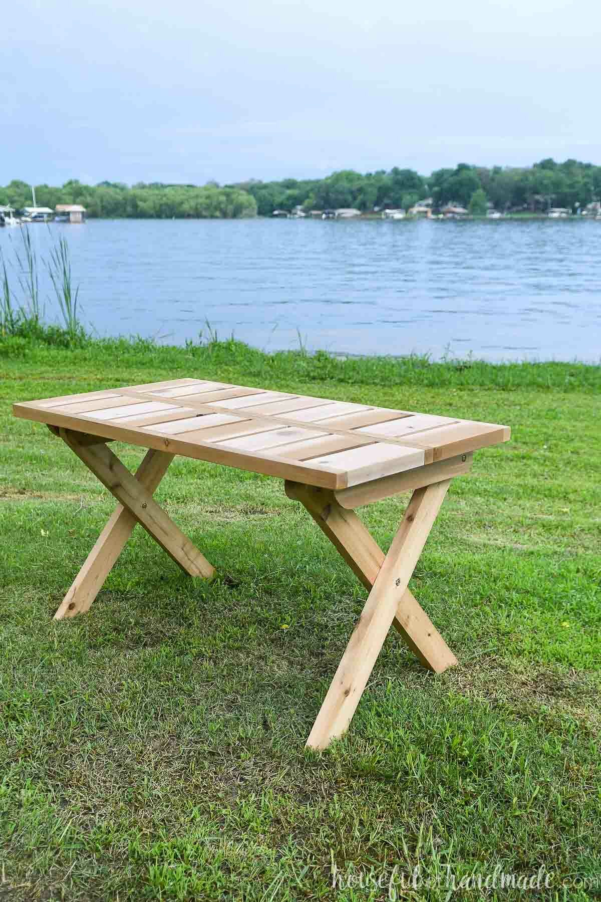 Cedar folding picnic table set up on the grass in front of a lake.
