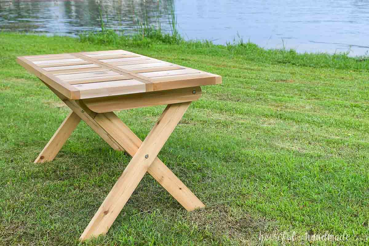 X-leg folding picnic table made from wood sitting on the lawn by a lake.