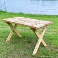 Wooden folding picnic table set up outside on the grass.