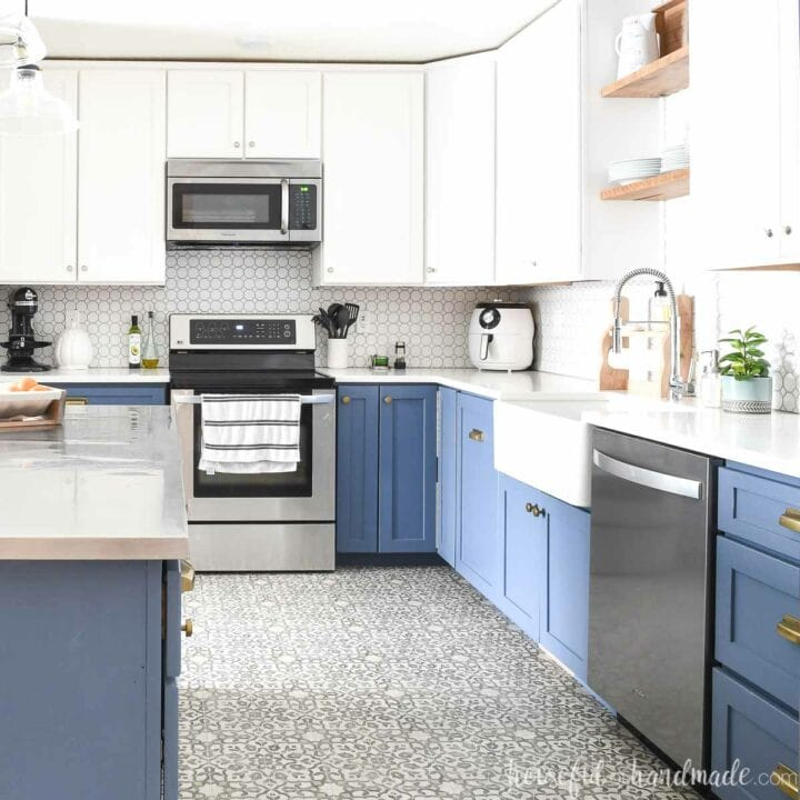 Blue and white kitchen cabinets in an open kitchen with full overlay cabinet doors.