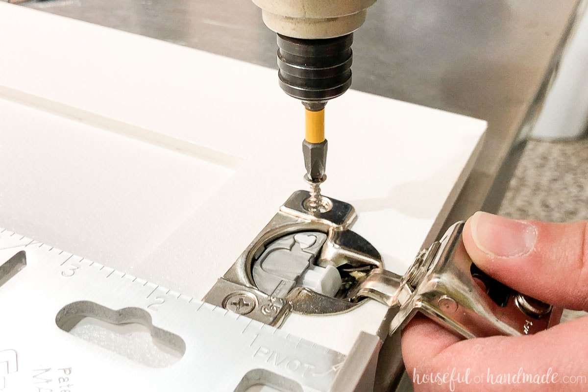 Attaching a concealed hinge to the back of a cabinet door.