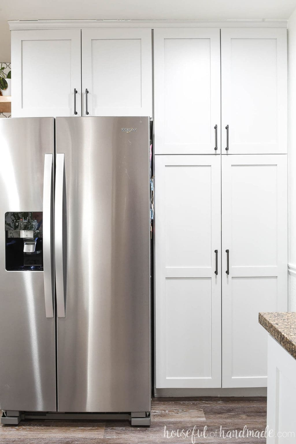 Bank of cabinets around a refrigerator with full overlay double cabinet doors.