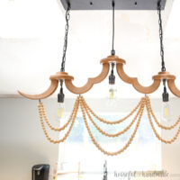 DIY wood chandelier with three light bulbs in a row and loops of wood beads draped below it.