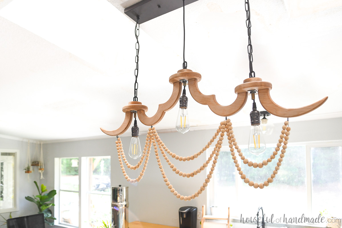 Wood beads hanging under eddison light bulbs in a DIY wood chandelier over a kitchen island.