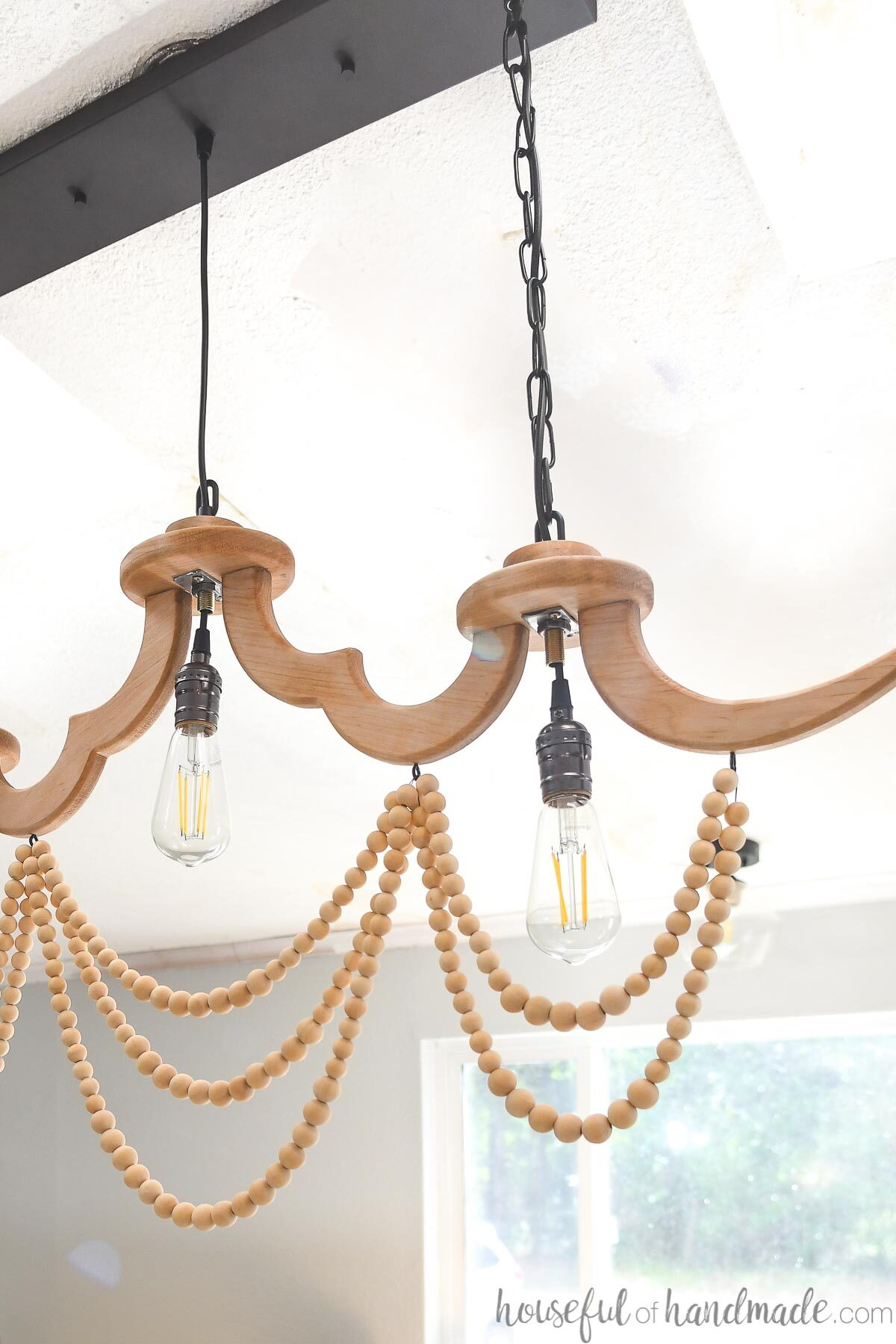 Half of the DIY linear chandelier with wood beads and eddison lightbulbs in it hanging on the ceiling.