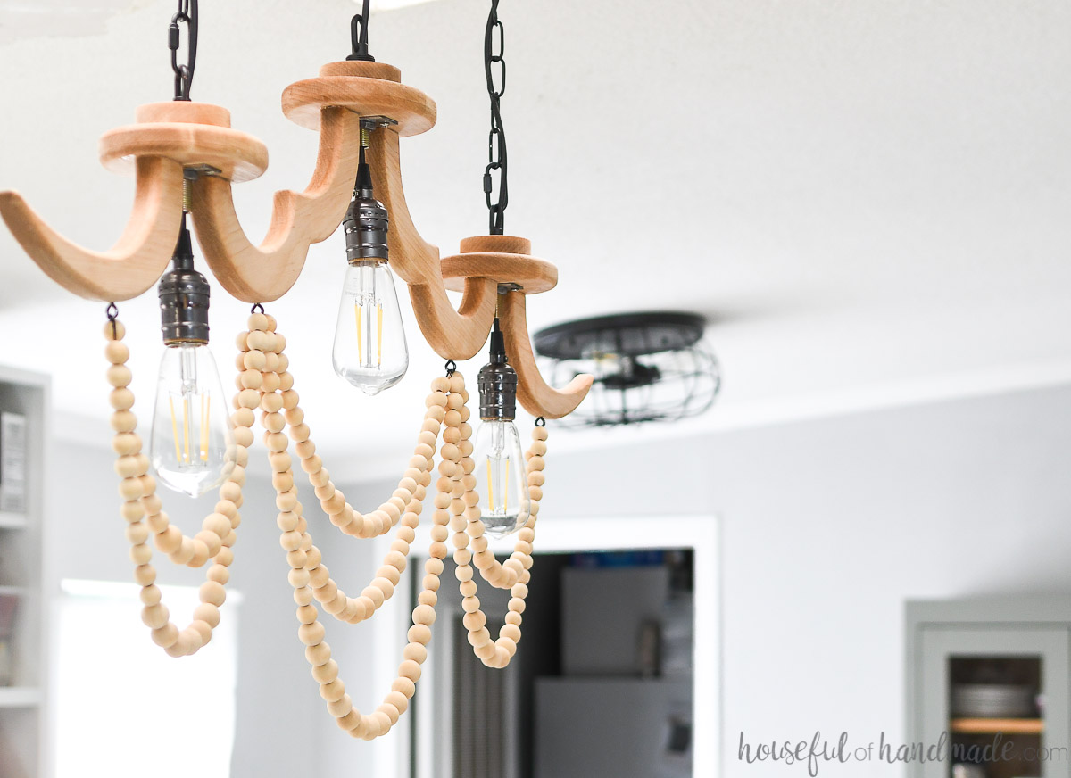 Angled view of the linear wood chandelier with 3 light bulbs and drapes of wood beads.