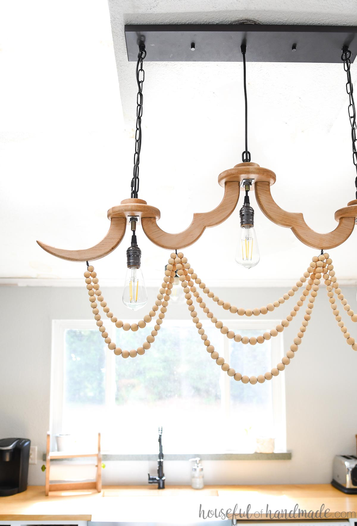 Straight on view of the DIY wood chandelier hanging above the kitchen island with the kitchen sink in the background.