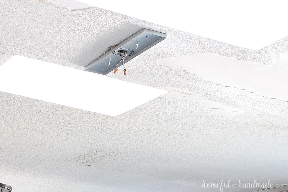 Linear pendant canopy inside piece mounted to the ceiling between two skylights.